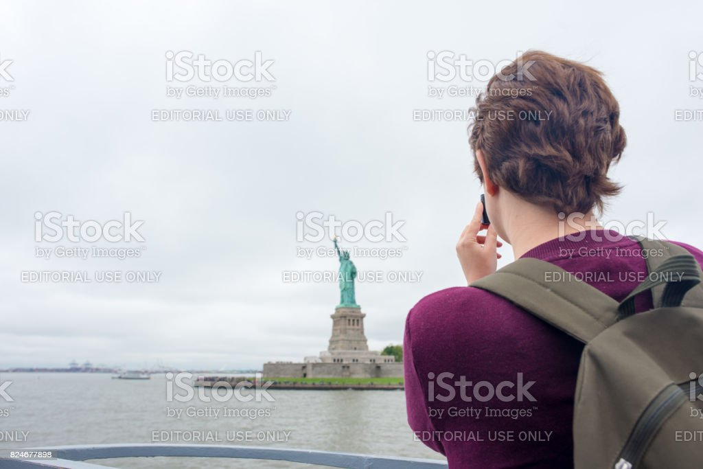 Tourist taking a photo of the Statue of Liberty stock photo