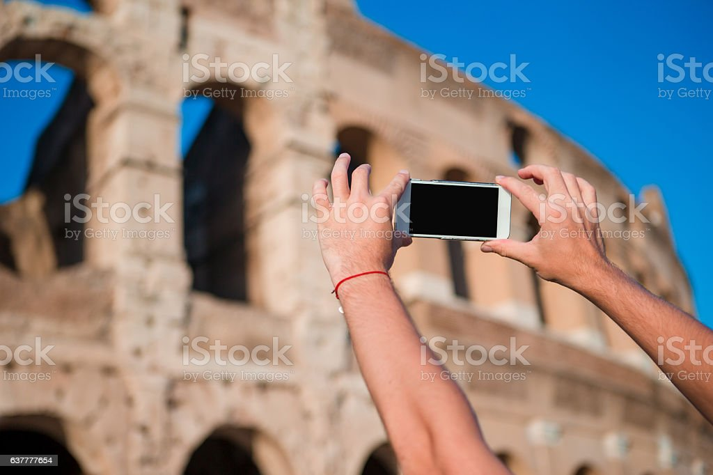 Tourist taking a picture by smartphone of Great Colosseum, Rome, stock photo