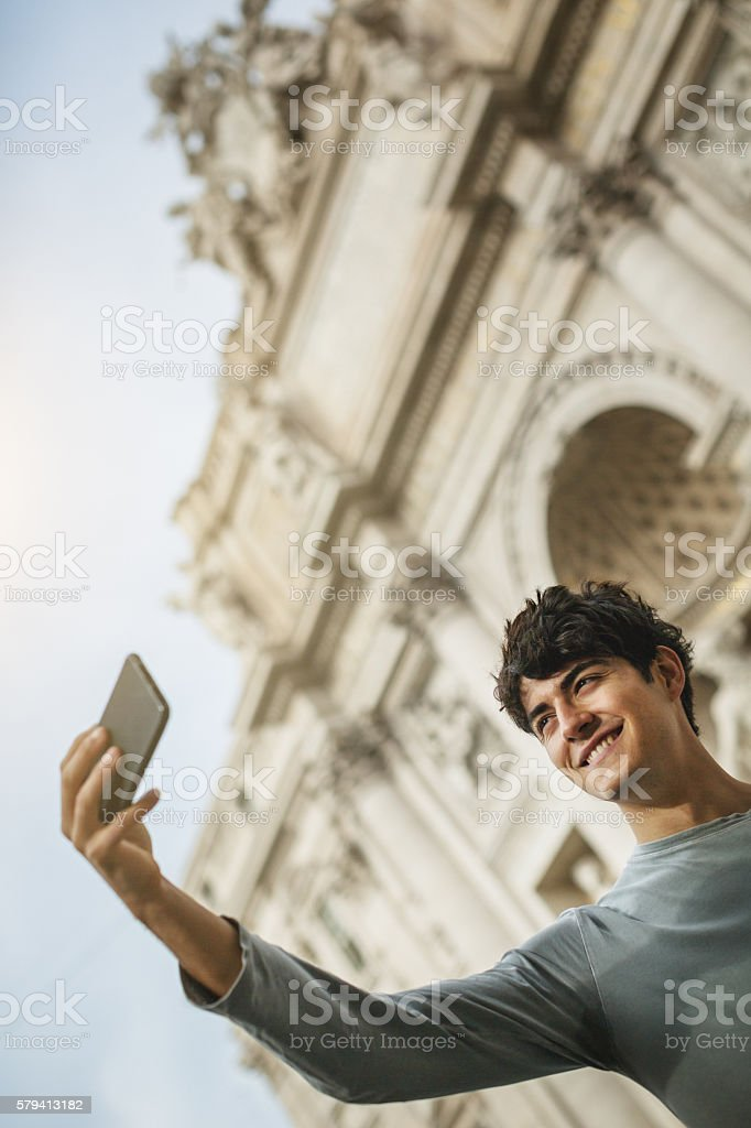 Tourist taking a selfie under Trevi fountain in Rome stock photo