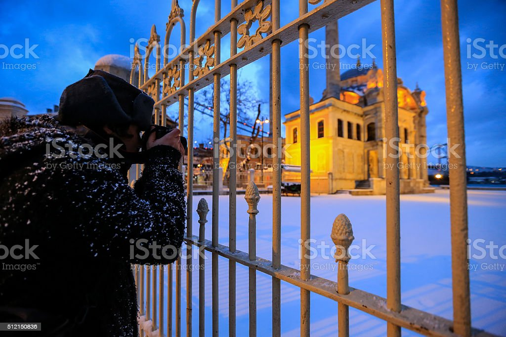 Tourist taking Ortaköy Mosque photo in winter, İstanbul stock photo