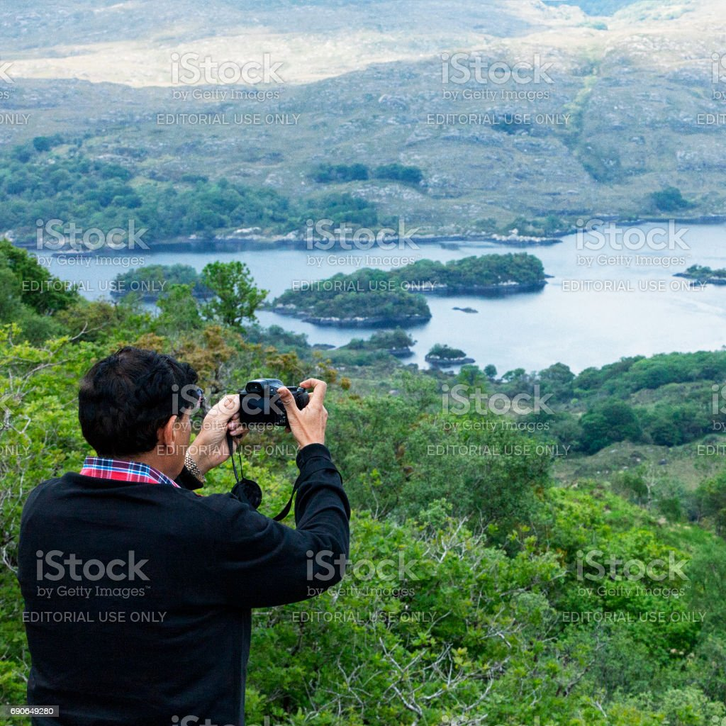 Tourist taking photo at Ladies View on the Ring of Kerry, Ireland stock photo