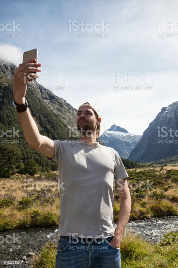 Tourist taking photo at Mount Talbot in Fiordland National Park, New Zealand stock photo