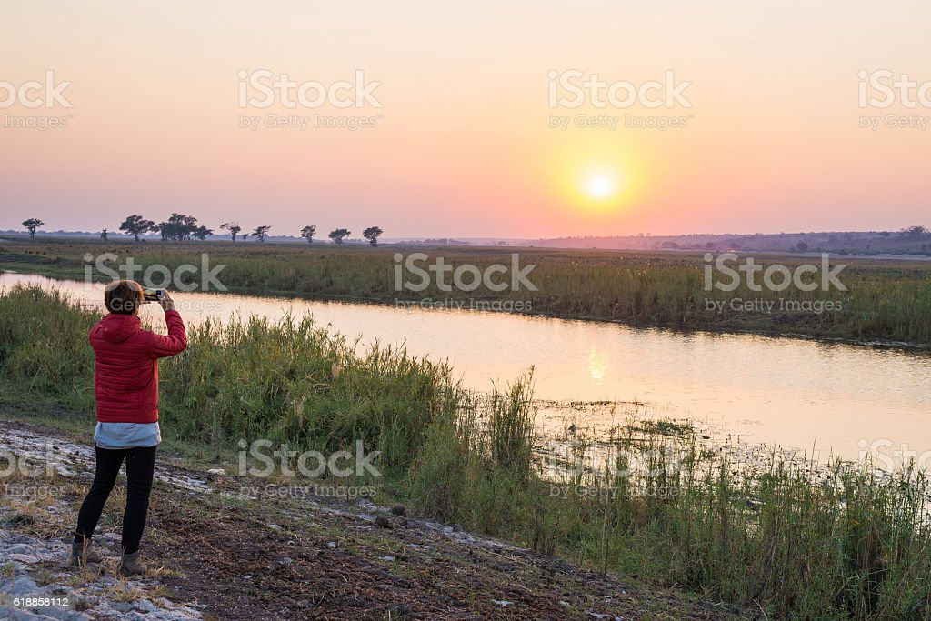 Tourist taking photo at sunset over Chobe River, Africa stock photo