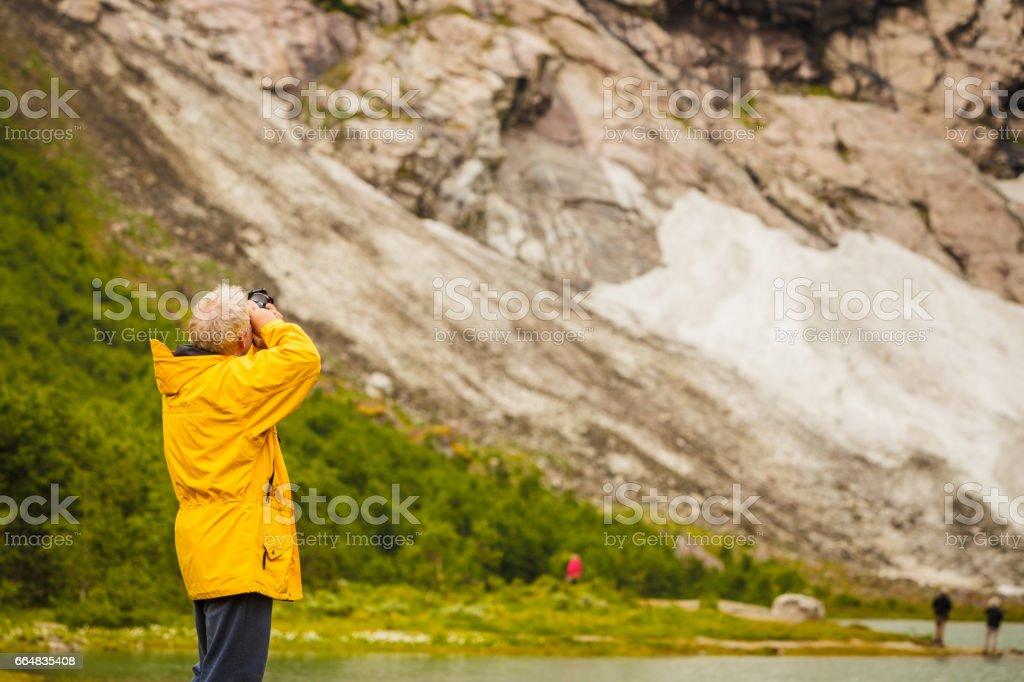 Tourist taking photo in norwegian mountains stock photo
