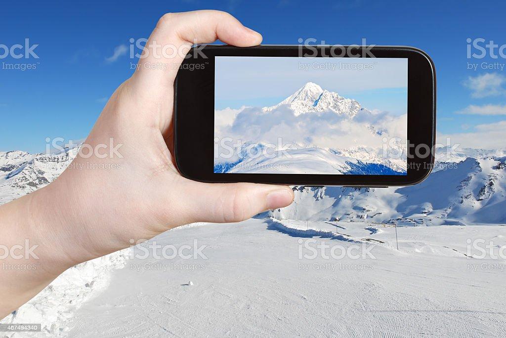 tourist taking photo of mountain peak in Alpes stock photo