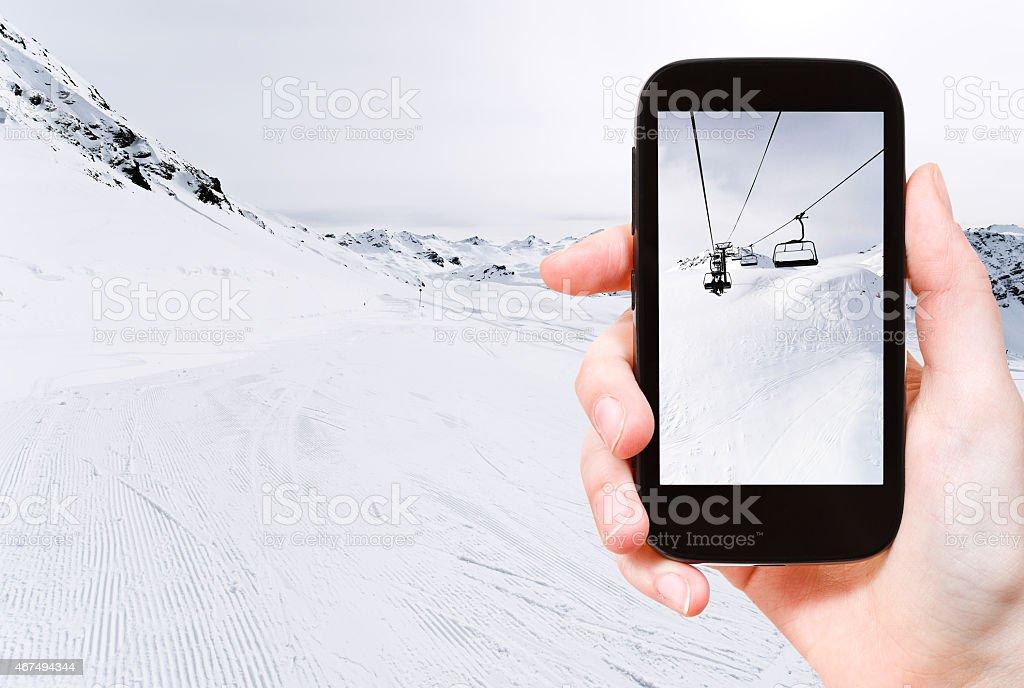tourist taking photo of skiing tracks and ski lift stock photo