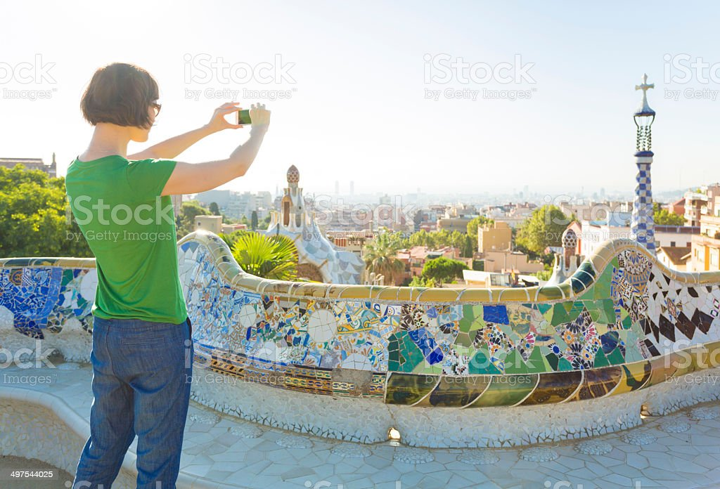 Tourist taking photos with smartphone in Gaudi's Park Guell, Barcelona stock photo