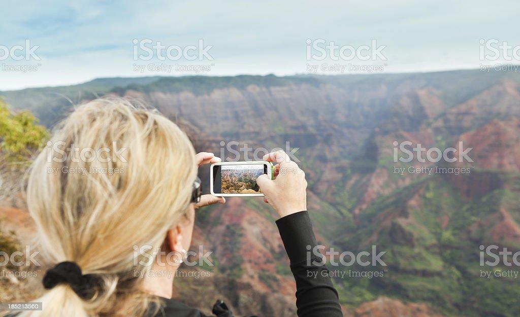 Tourist Taking Picture of the Waimea Canyon in Kauai Hawaii stock photo