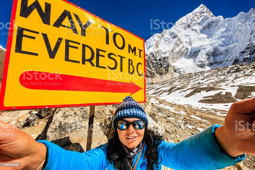 Tourist taking selfie next to signpost 'Way to MountEverest BaseCamp' stock photo