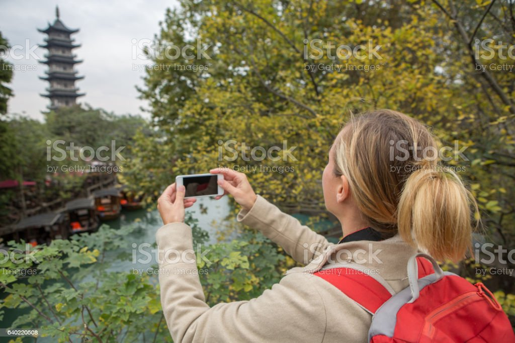 Tourist taking smart phone picture in Chinese village stock photo