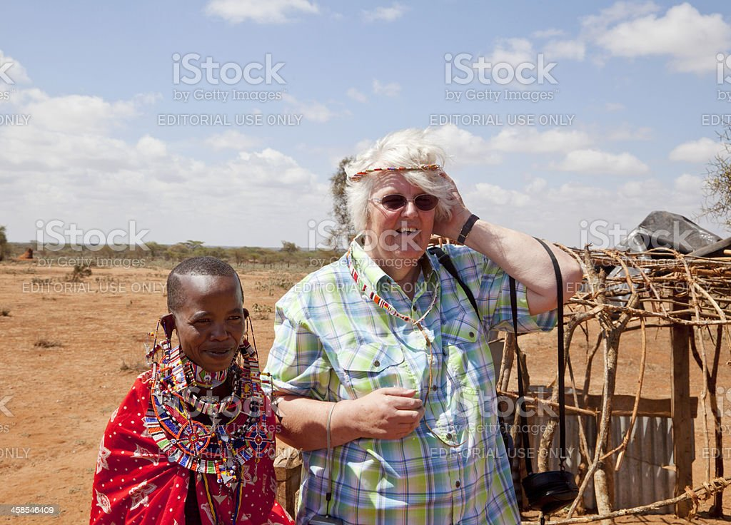 Tourist trying traditional jewellry standing next to a masai woman. stock photo
