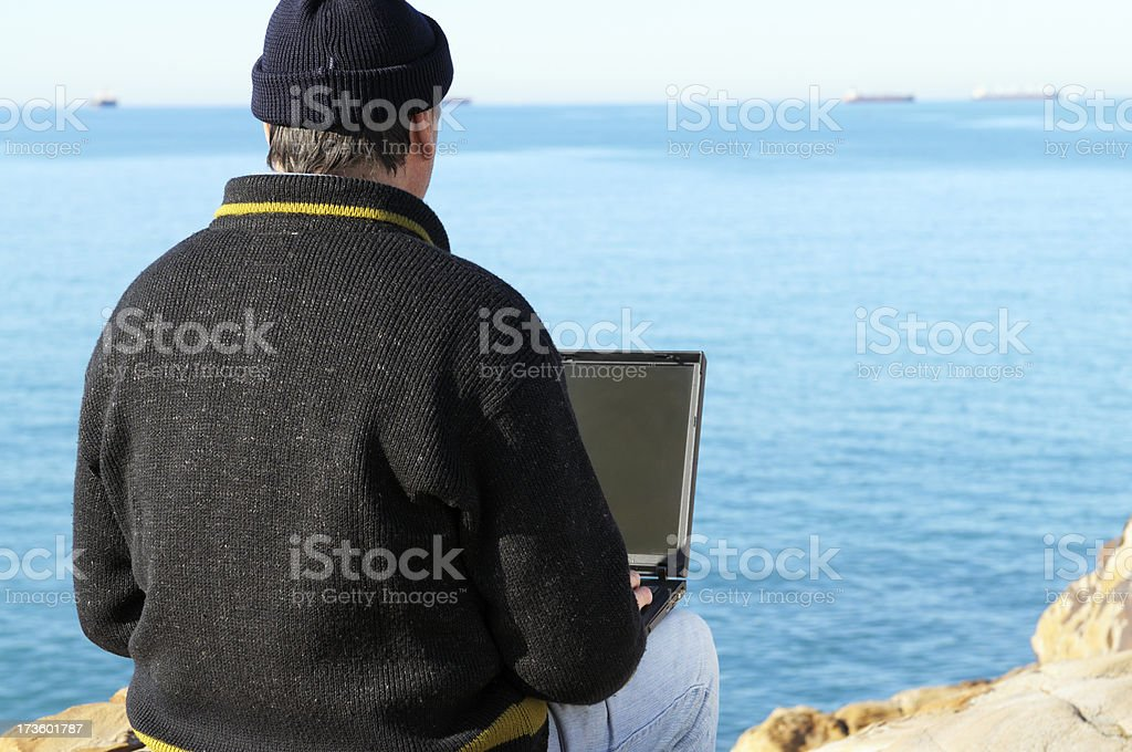 Tourist Using PC In Front Of The Sea royalty-free stock photo