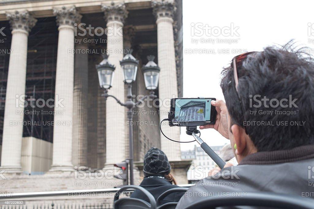 Tourist using selfie-stick with phone stock photo