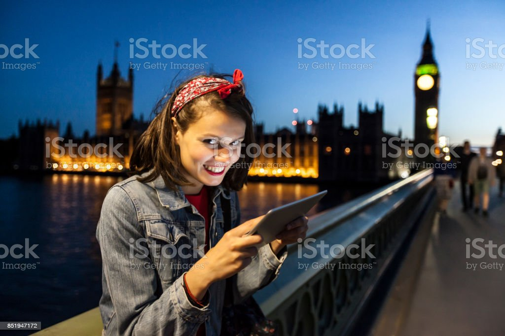 Tourist using tablet on bridge at night stock photo