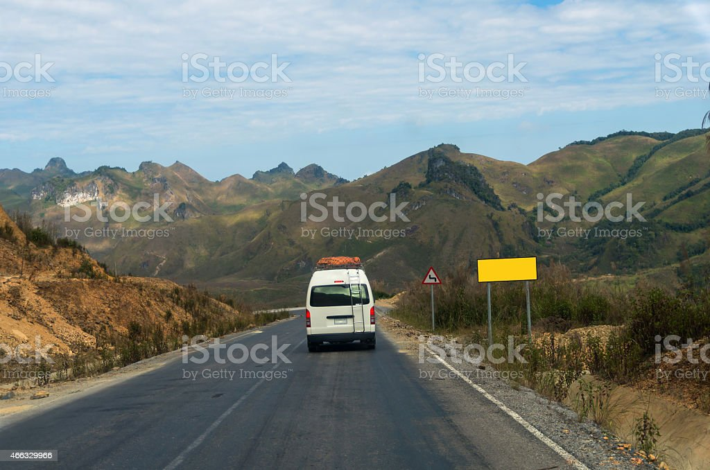 Tourist Van on the highway with traffic sign and mountain stock photo