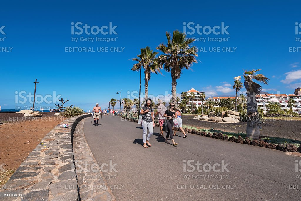 Tourist walking in Las Americas coastline in Tenerife South area. stock photo