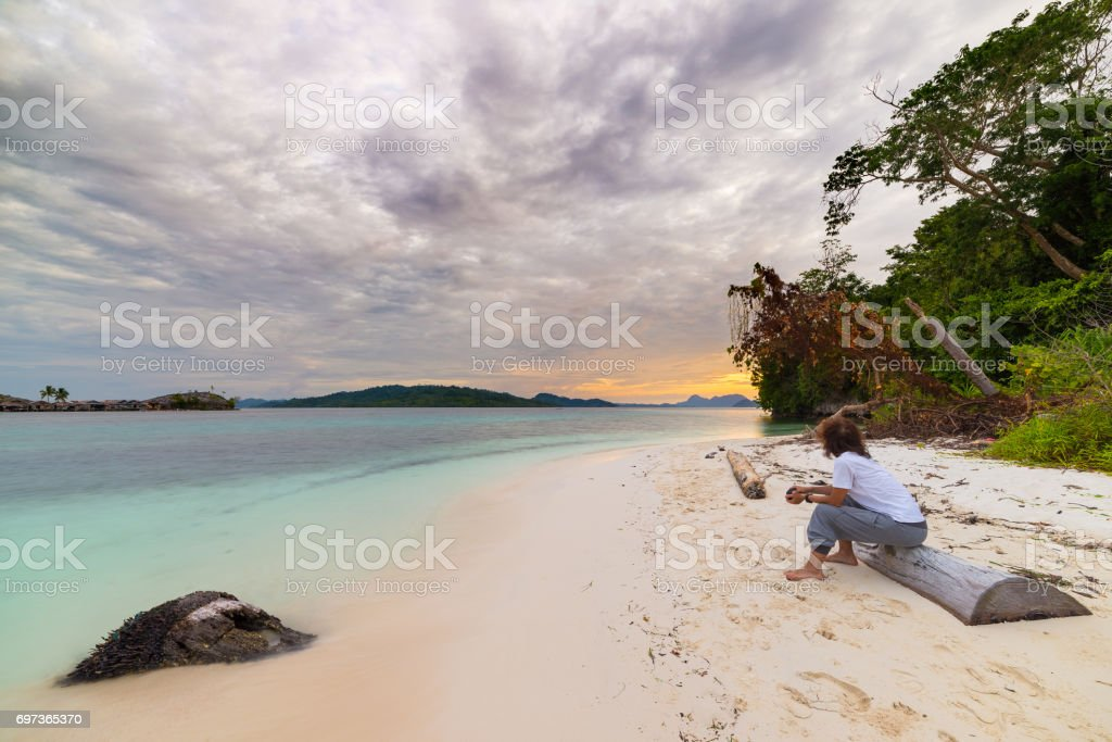 Tourist watching a relaxing sunset sitting on the beach in the remote Togean Islands, Central Sulawesi, Indonesia, upgrowing travel destination in recent years. Wide angle view. stock photo