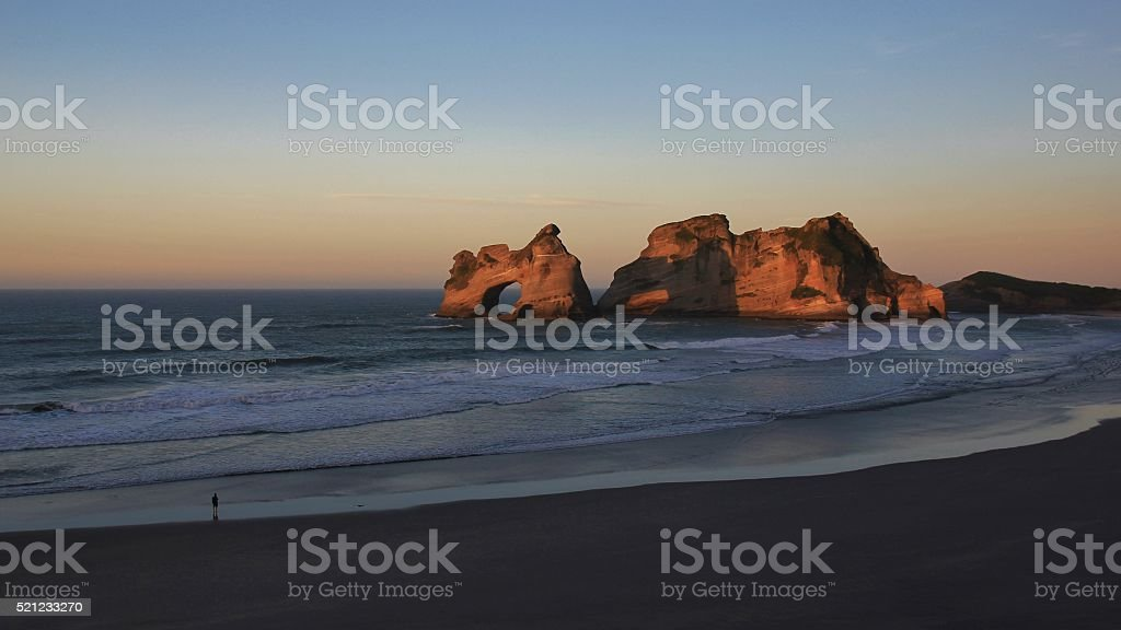 Tourist watching sunset at Wharariki Beach stock photo