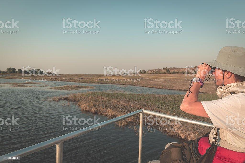 Tourist watching wildlife by binocular on Chobe River stock photo