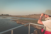 Tourist watching wildlife by binocular on Chobe River