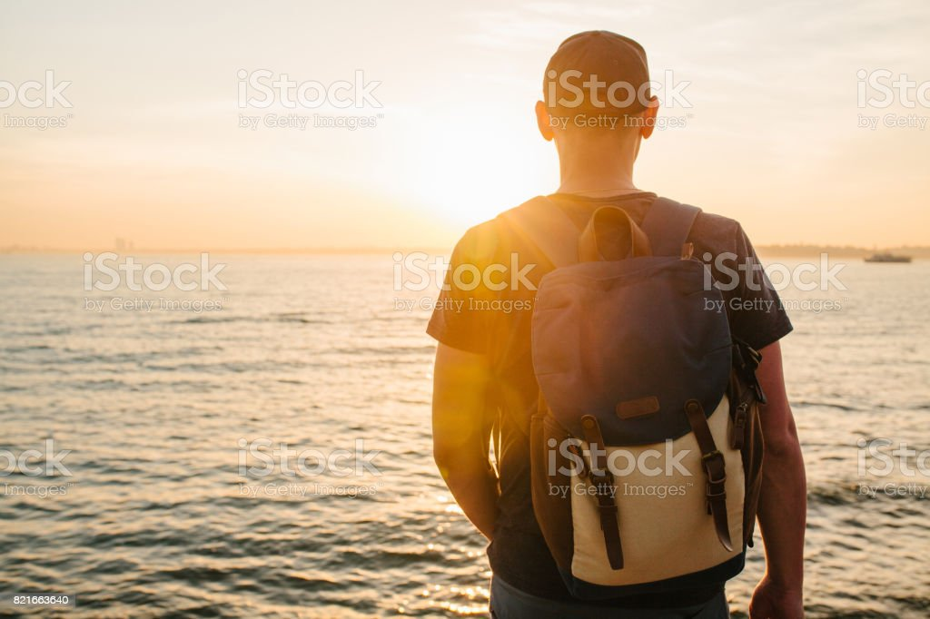 A tourist with a backpack on the coast. Travel, tourism. On the...