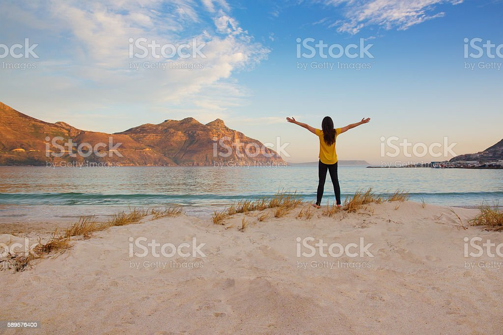 Tourist with arms up at Hout Bay beach at dusk stock photo