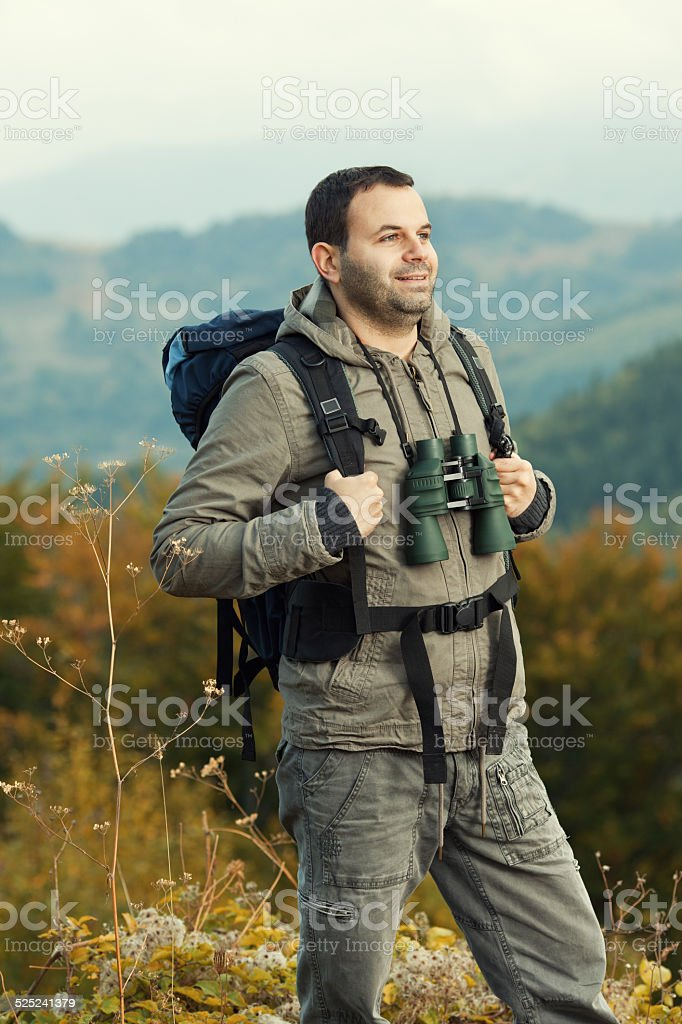 Tourist with backpack and binoculars stock photo