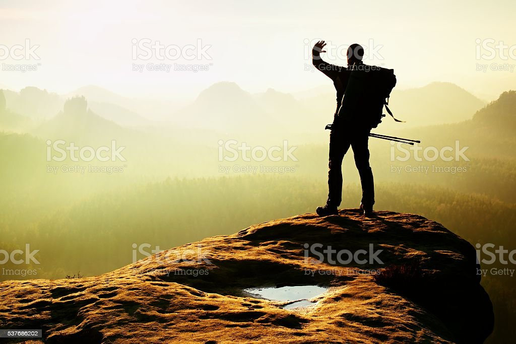 Tourist with backpack and poles in hand shadowing eyes. stock photo