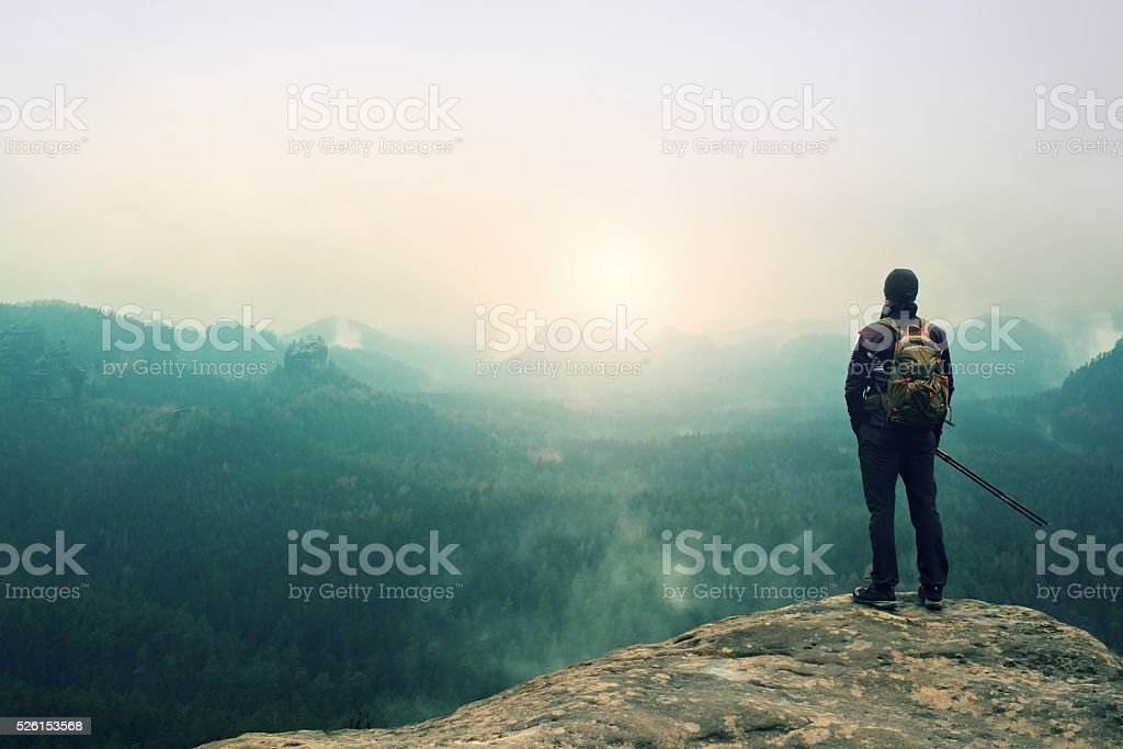Tourist with backpack and poles on cliff watching into valley stock photo