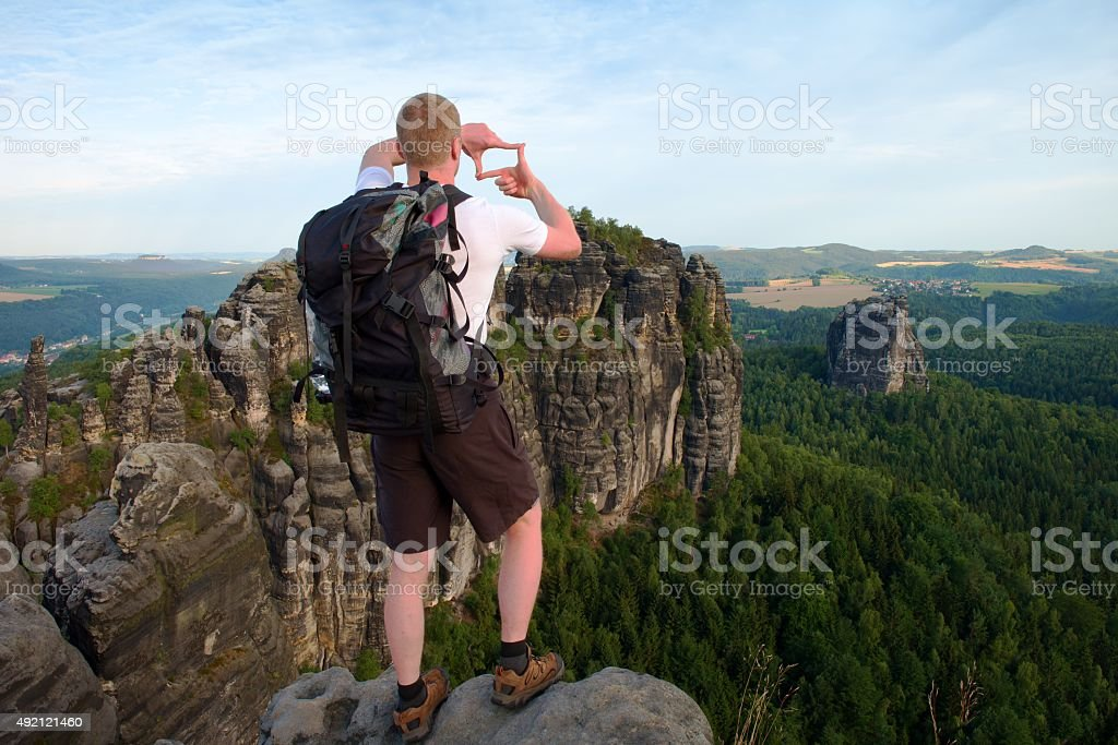 Tourist with backpack make frame with fingers on both hands. stock photo