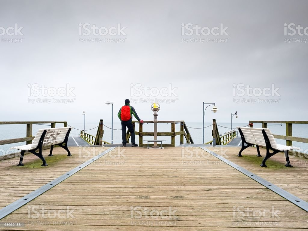 Tourist with backpack on wooden sea pier. Man, trekking suit stock photo