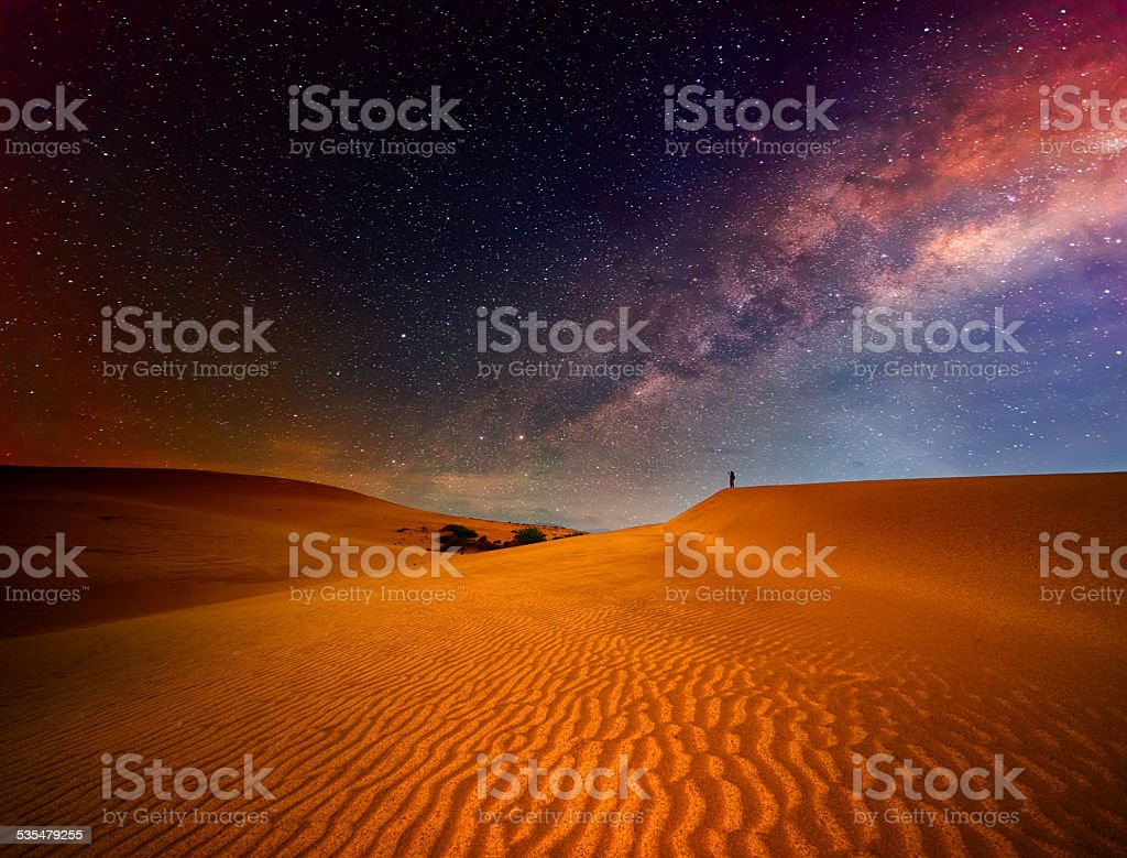 Tourist with backpack standing on top of mountain and enjoying stock photo