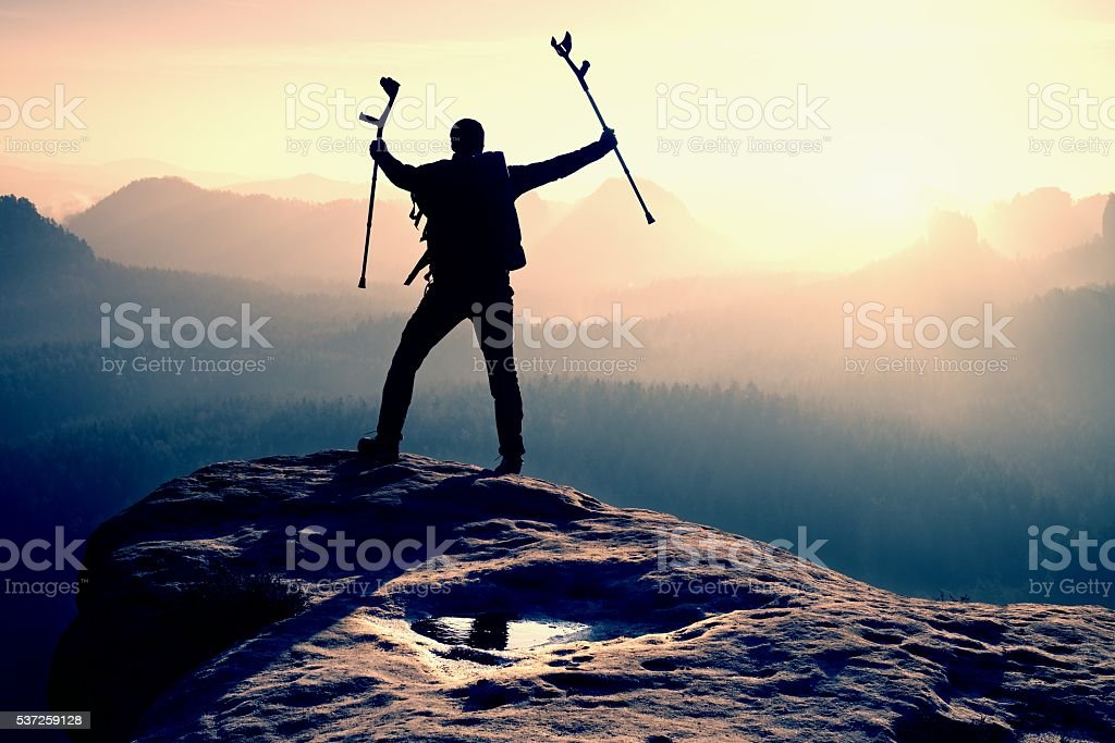 Tourist with  crutch above head achieved peak with broken leg stock photo