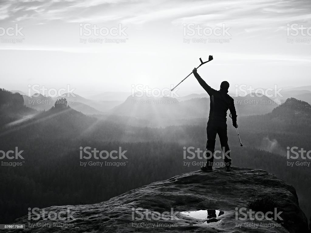 Tourist with forearm crutch above head achieved mountain peak stock photo