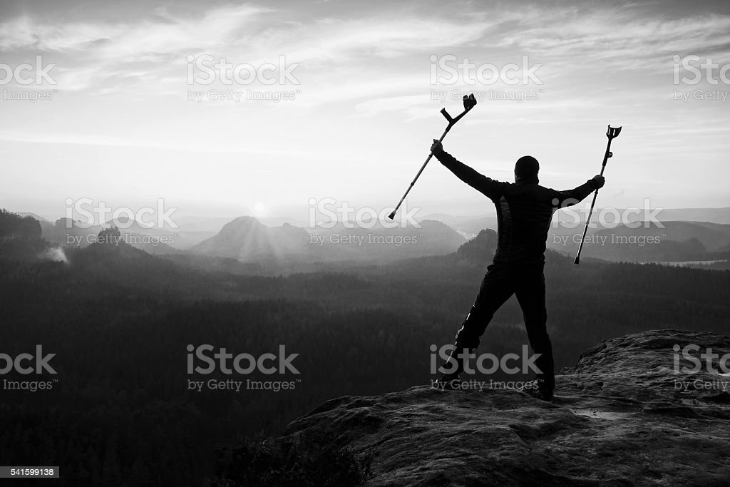 Tourist with forearm crutch achieved mountain peak with broken leg stock photo