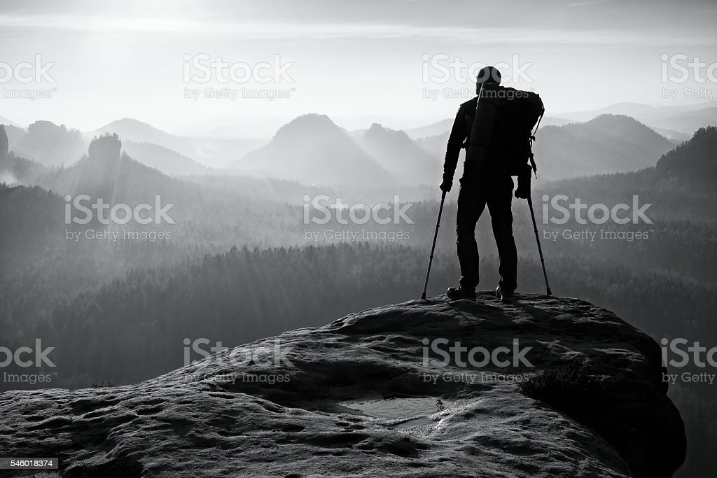 Tourist with leg in immobilizer. Hiker silhouette with medicine crutch stock photo