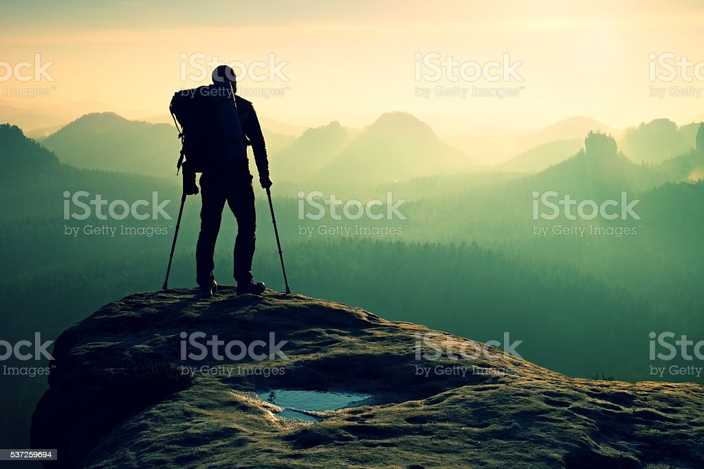 Tourist with leg in immobilizer with medicine crutch on mountain stock photo