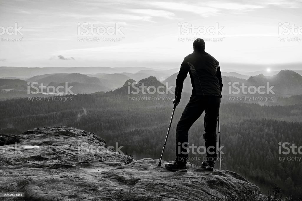 Tourist with  medicine crutch on mountain peak. Deep misty valley stock photo