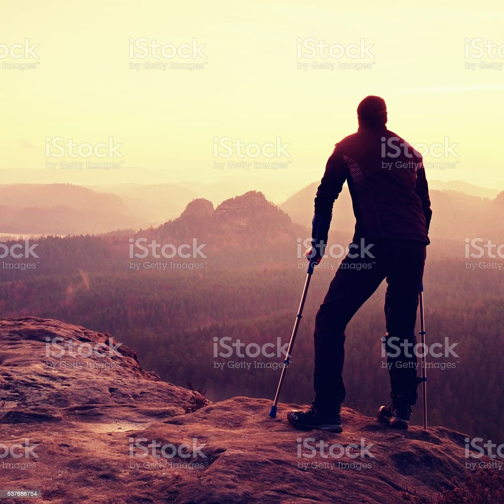 Tourist with  medicine crutch on mountain peak. Deep valley bellow stock photo