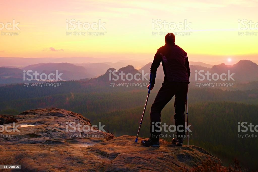 Tourist with  medicine crutch on peak. Misty mountains summits stock photo