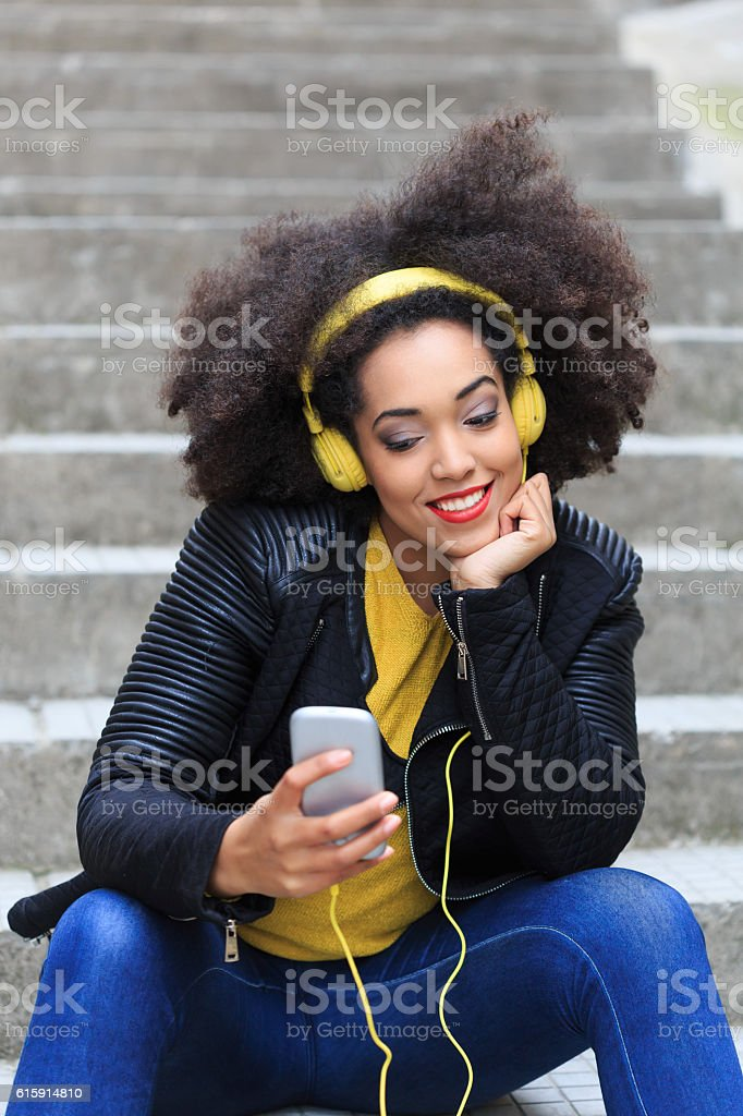 Tourist with yellow headphones sitting on stairs stock photo