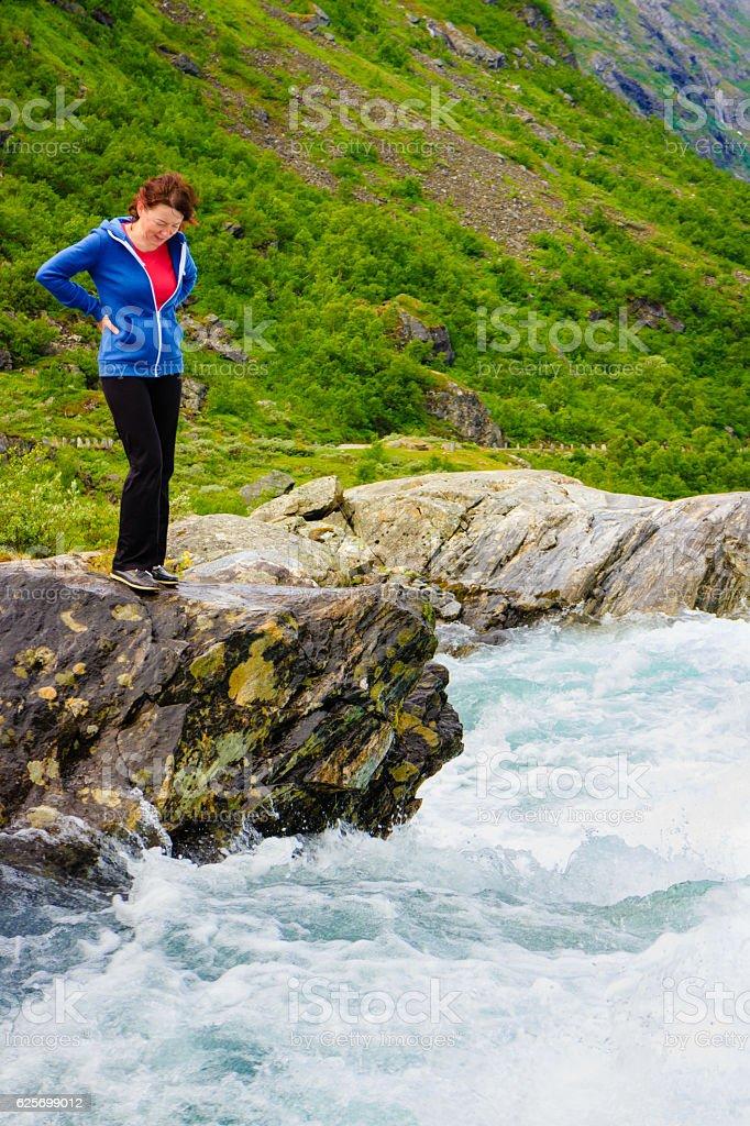 Tourist woman by Videfossen Waterfall in Norway stock photo