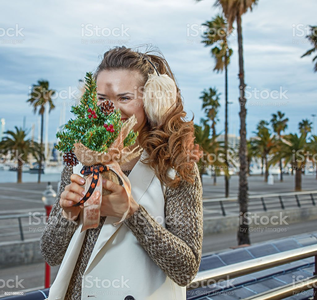 tourist woman in Barcelona hiding behind a little Christmas tree stock photo