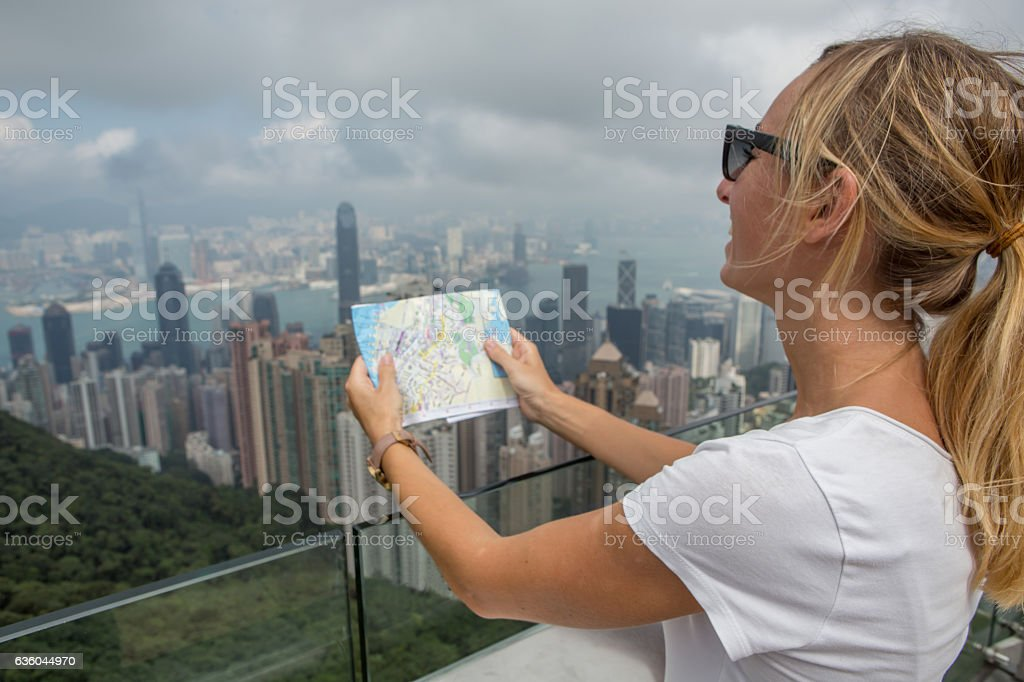 Tourist woman in Hong Kong looks at map stock photo