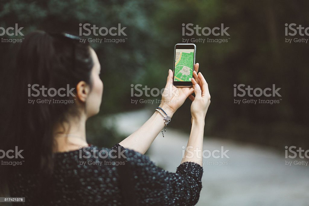 Tourist woman navigating the city park with a map stock photo