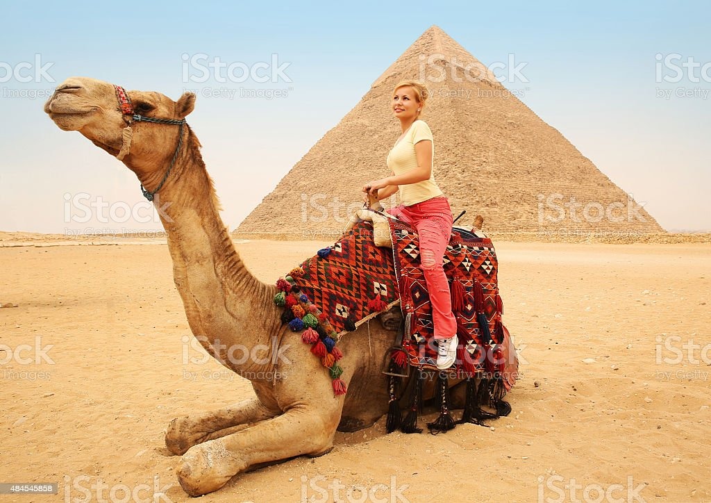 Tourist woman on camel in Giza. Blonde near Pyramid, Egypt stock photo