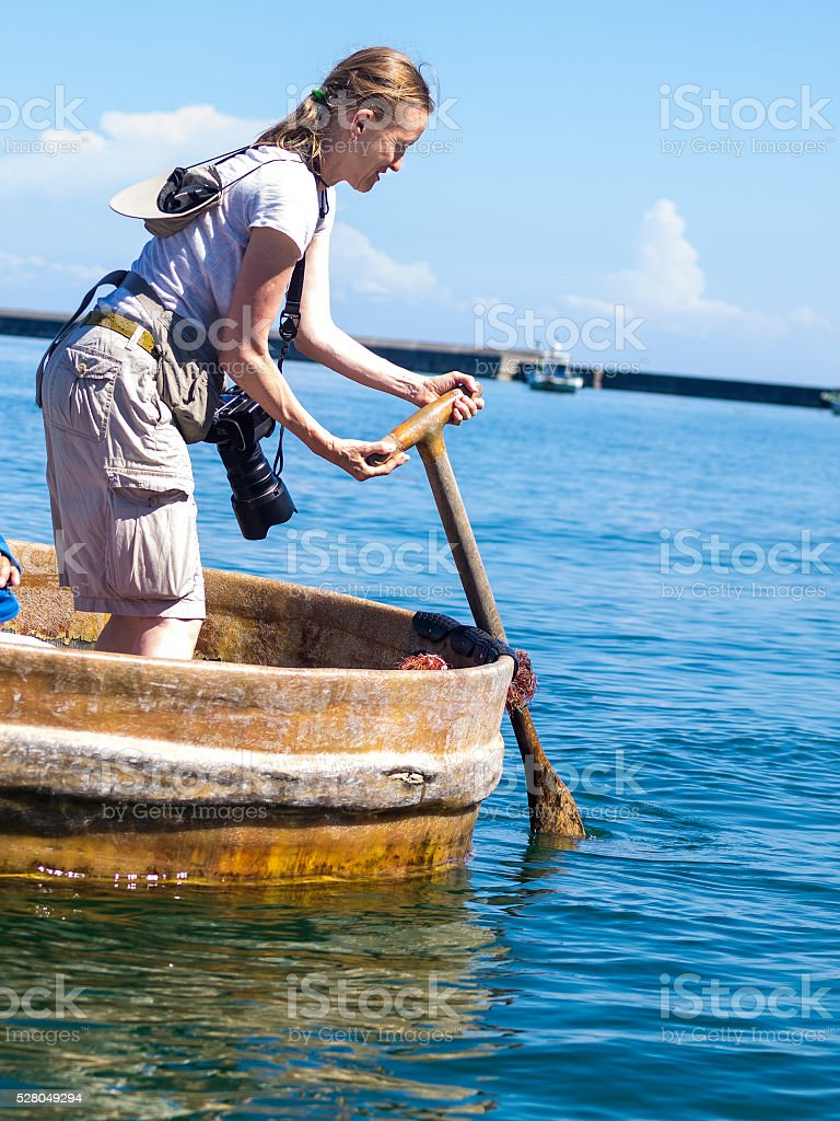 Tourist woman paddling Tub-shaped boat in Japan sea stock photo