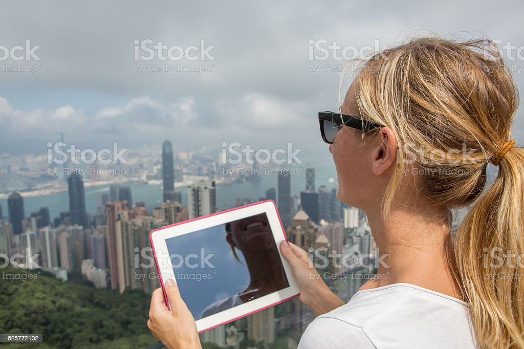 Tourist woman photographing Hong Kong landscape with digital tablet stock photo