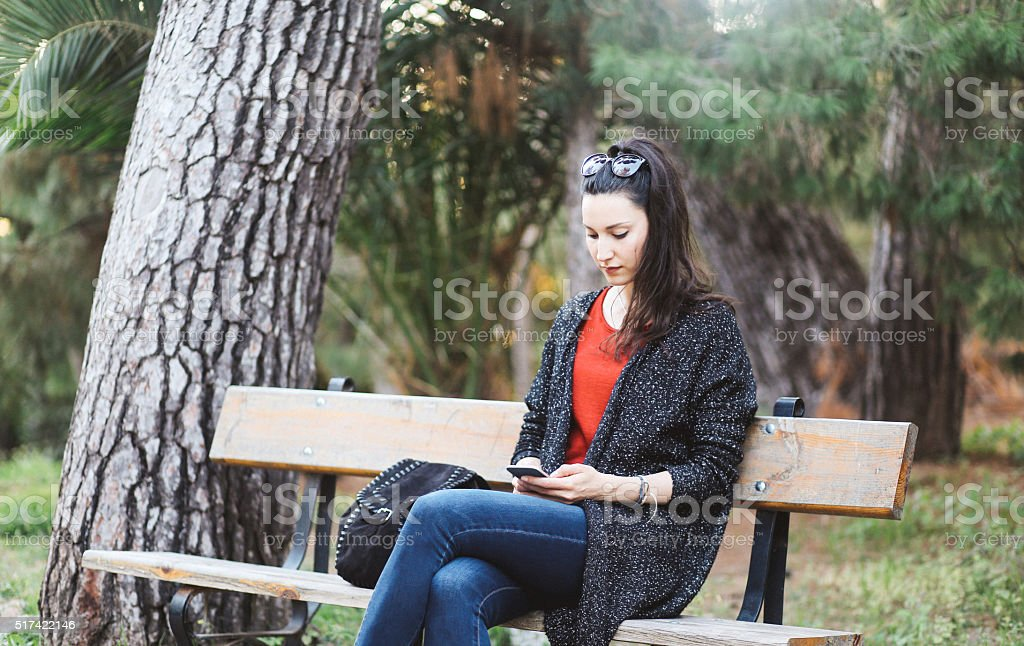 Tourist woman relaxing in the park and checking messages stock photo