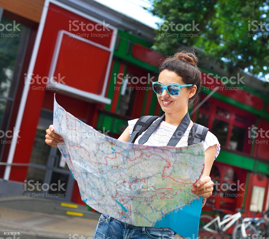Tourist woman searching direction on location map stock photo